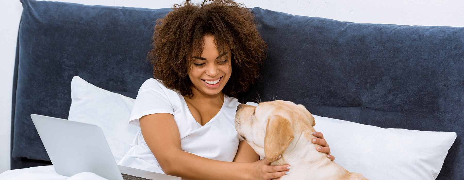 Woman holding he laptop and petting her dog on a bed